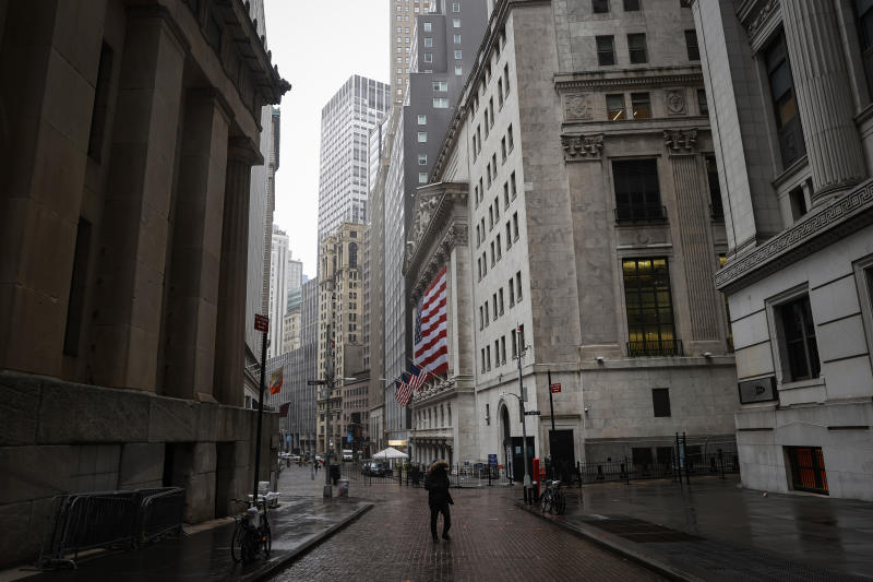 A pedestrian walks on an nearly empty Wall St., near the New York Stock Exchange (NYSE) as the coronavirus disease (COVID-19) outbreak continues in New York City, New York, U.S., March 23, 2020. REUTERS/Mike Segar