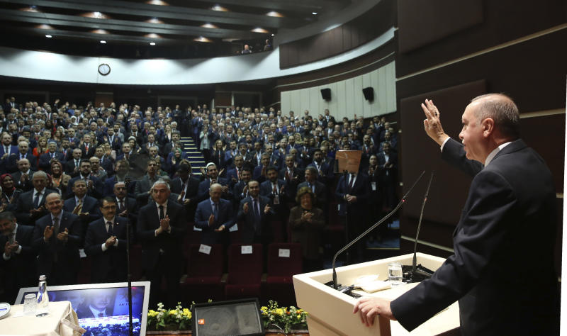 "Turkey's President Recep Tayyip Erdogan gestures as he addresses the members of his ruling party, in Ankara, Turkey, Thursday, Dec. 26, 2019. Erdogan says Thursday his government will submit a bill to parliament that would allow Turkey to send troops to Libya, in support of the U.N.-backed government there. Erdogan said the Libyan government, which controls the capital, Tripoli, has ""invited"" Turkey to send troops. (Turkish Presidency via AP, Pool)"