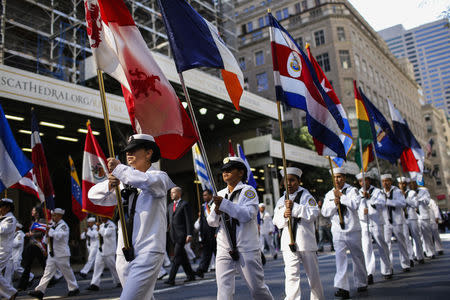 People walk with flags as they take part in the annual Hispanic Day Parade in New York