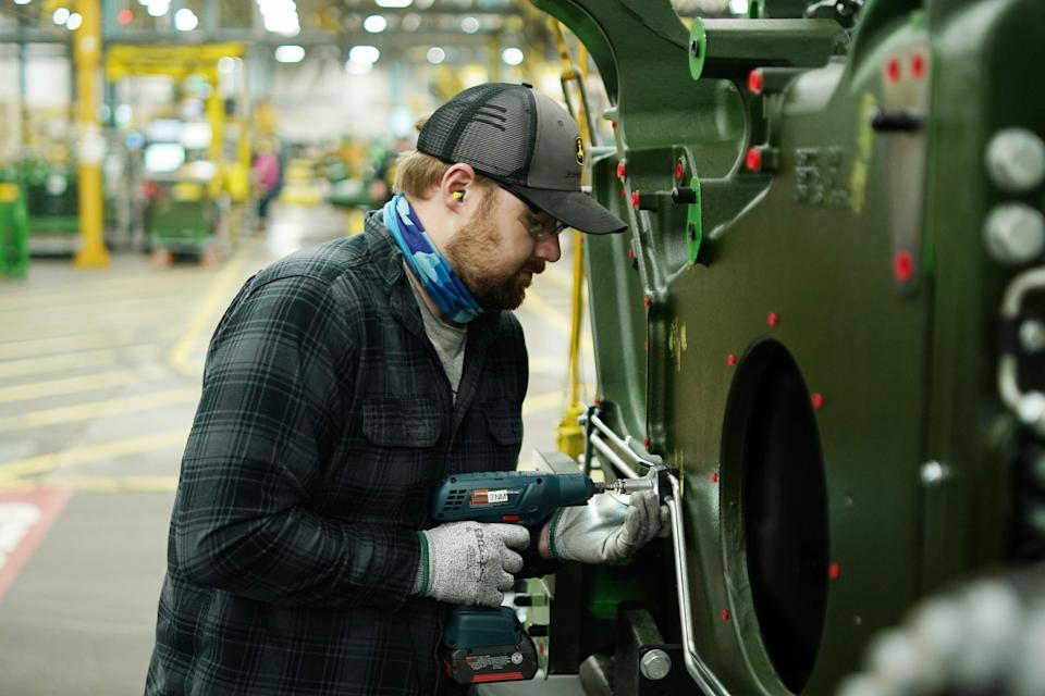 Operator Chris Smith installs a clamp that holds together hydraulic lines on an 8RT tractor chassis.
