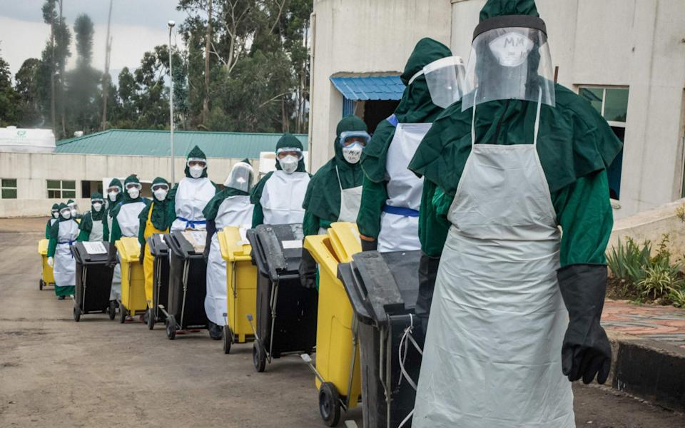 Cleaning staff in carry lidded trash boxes to minimize contamination in Addis Ababa - AMANUEL SILESHI/AFP