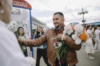 Stsiapan Latypau smiles while presenting flowers to women during a protest in Minsk, Belarus, Wednesday, Aug. 12, 2020. Latypau tried to slice his throat with a pen in court on Tuesday, June 1, 2021 after being put in a cell with mentally deranged inmates and threatened with criminal reprisals against his family. The 41-year-old Stsiapan Latypau was hospitalized and put in a medically induced coma after the incident. Political prisoners in Belarus are coming under increasing pressure following the recent arrest of activist Raman Pratasevich from a forcibly diverted Ryanair flight. (AP Photo)