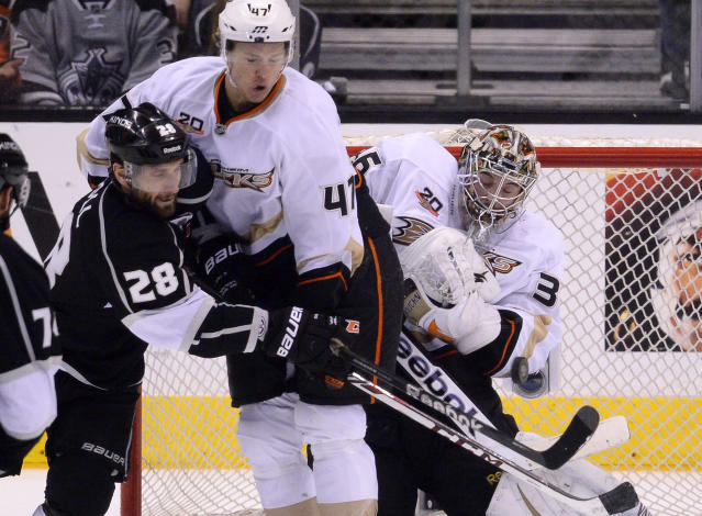 Los Angeles Kings center Jarret Stoll, left, tries to get a shot in on Anaheim Ducks goalie John Gibson, right, as defenseman Hampus Lindholm, of Sweden, defends during the second period in Game 4 of an NHL hockey second-round Stanley Cup playoff series, Saturday, May 10, 2014, in Los Angeles. (AP Photo/Mark J. Terrill)