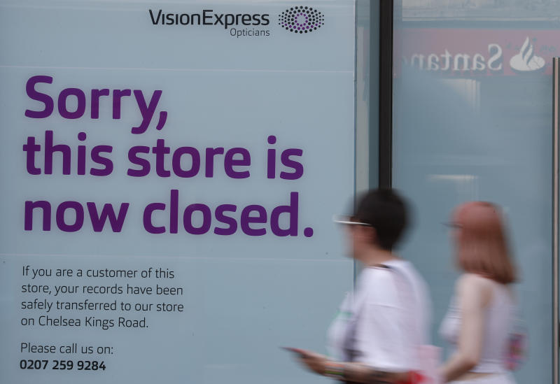 Pedestrians pass by a closed branch of Vision Express in Kensington, London, Wednesday, Aug. 12, 2020. The British economy is on course to record the deepest coronavirus-related slump among the world's seven leading industrial economies after official figures showed it shrinking by a 20.4% in the second quarter of 2020 alone said The Office for National Statistics. (AP Photo/Alastair Grant)