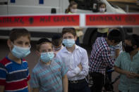 Ultra-Orthodox Jewish children wear face masks amid the coronavirus pandemic as they gather in Bnei Brak, Israel Sunday, Sept. 6, 2020. The death toll from the coronavirus in Israel has surpassed 1,000, as the government on Sunday mulled steps for imposing new restrictions to quell a resurgence in infections. (AP Photo/Ariel Schalit)
