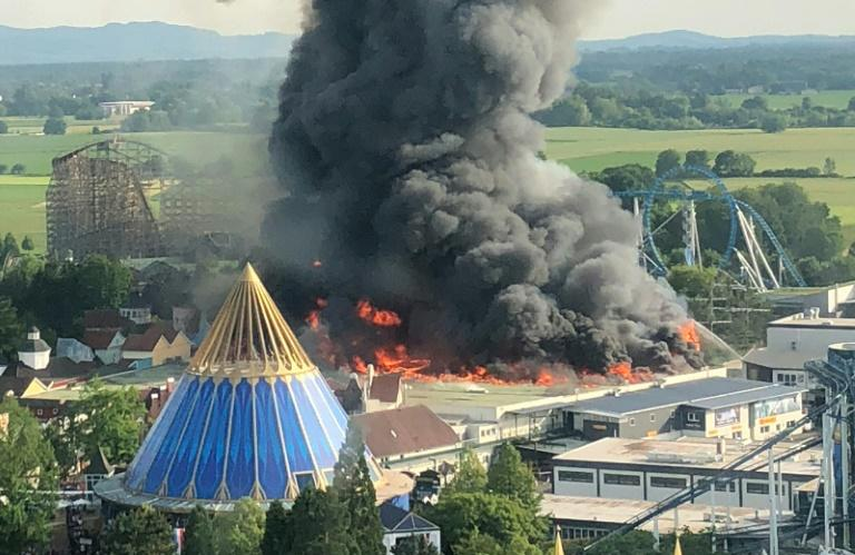 A black column of smoke rises from a warehouse in flames above Europa-park in Rust, southern Germany