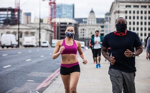 Joggers in central London wearing anti-pollution masks - Credit: Getty