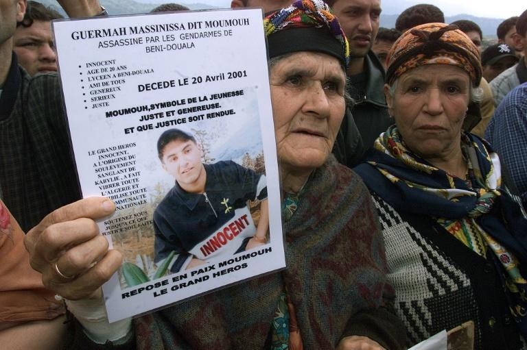 The grandmother of Massinissa Guermah, a teenager killed by Algerian police in April 2001, holds aloft his picture in May that year, amid protests in the country's Berber heartland