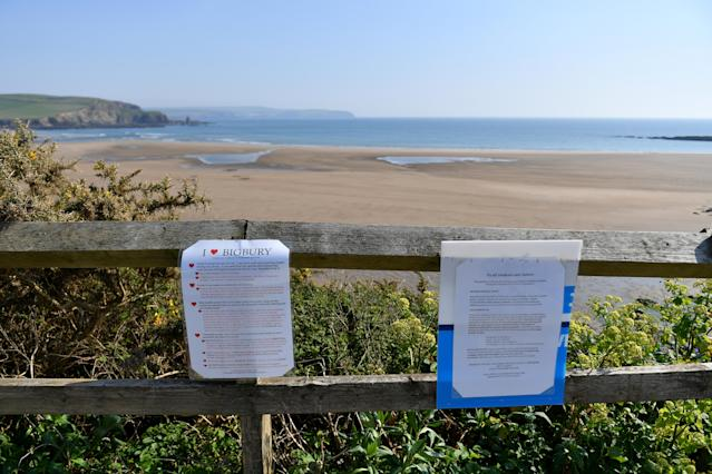 Signs displayed informing visitors of COVID-19 measures above a deserted Bigbury Beach in Devon. (Getty)