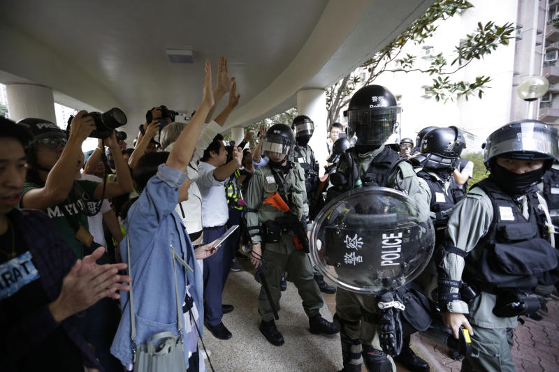 Angry residents raise their hands to protest police presence in their neighborhood in Hong Kong, Sunday, Nov. 10, 2019. Authorities in Hong Kong have closed a subway station after protesters broke windows and damaged ticket machines. The semi-autonomous territory is in the sixth month of protests that began over a proposed China extradition law and have expanded to include demands for greater democracy and other grievances. (AP Photo/Dita Alangkara)