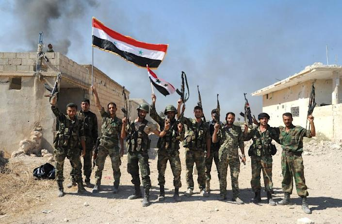 Syrian forces celebrate after capturing Atshan village as part of a major ground offensive in central Hama province, on October 11, 2015 (AFP Photo/)