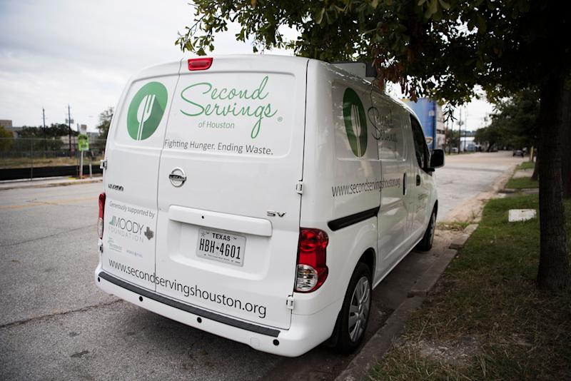 "A van owned by ""Second Servings,"" an organization that picks up leftover food and gives it to those in need, is parked at Midtown Park in Houston."