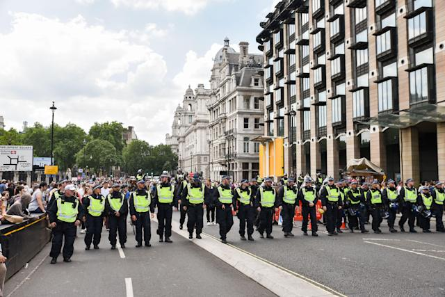 <p>Police officers form a line to keep anti-fascist groups from confronting a demonstration by Trump supporters and a Free Tommy Robinson group on Whitehall, London, July 14, 2018. (Photo: Matthew Chattle/REX/Shutterstock) </p>