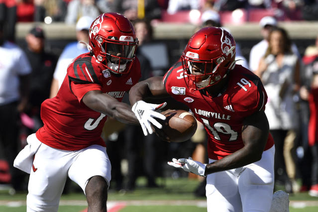 Louisville quarterback Micale Cunningham (3) hands the ball off to running back Hassan Hall (19) during the first half of an NCAA college football game in Louisville, Ky., Saturday, Oct. 19, 2019. (AP Photo/Timothy D. Easley)