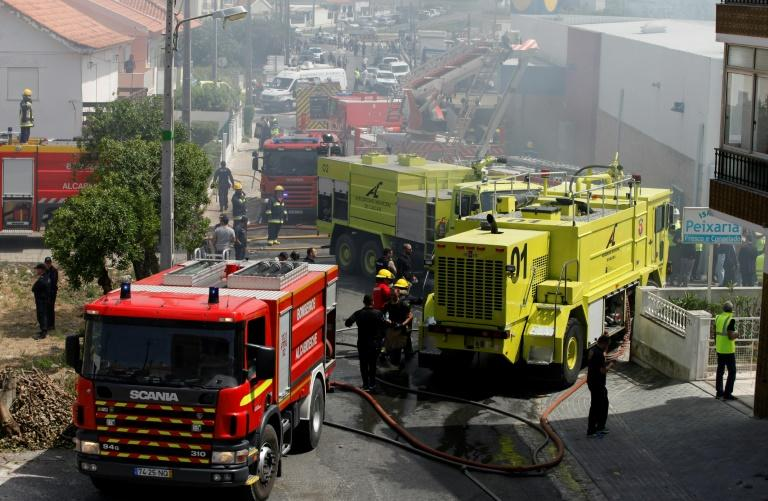 Rescue crews work after a plane crashed into a supermarket warehouse in Tires, near Sintra on April 17, 2017
