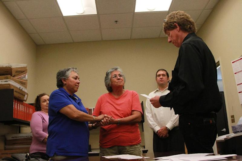 Catherine Martinez and Linda Montoya hold hands as Dona Ana County employee and reverend Jess C. Williams marries them at the Dona Ana County Clerk's Office in Las Cruces, New Mexico, Wednesday, Aug. 21, 2013. More than 40 same-sex couples obtained their marriage licenses after the county clerk announced the county would be the first in New Mexico to marry same-sex couples. (AP Photo/Juan Carlos Llorca)