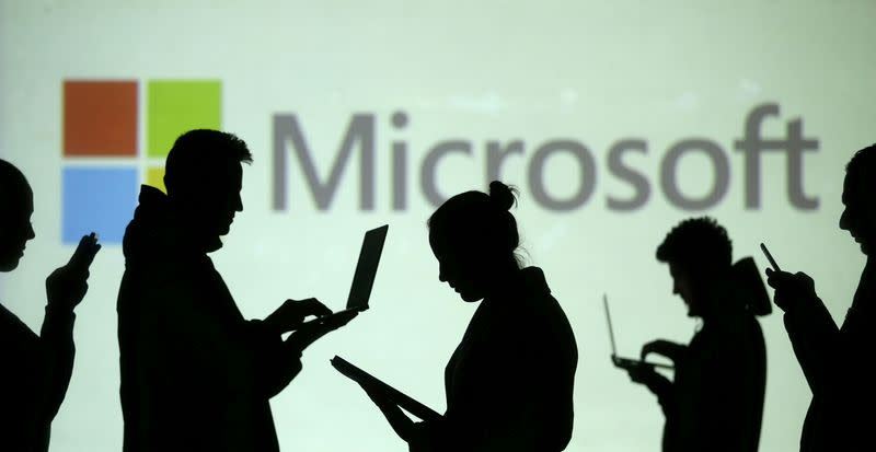 FILE PHOTO: Silhouettes of laptop and mobile device users are seen next to a screen projection of Microsoft logo