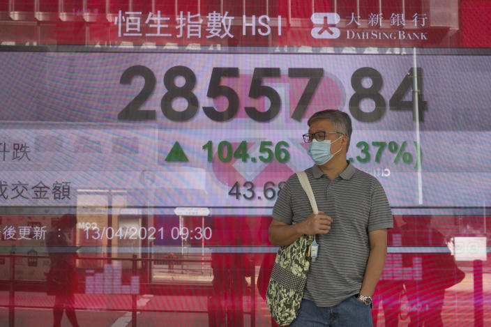 A man wearing a face mask walks past a bank's electronic board showing the Hong Kong share index at Hong Kong Stock Exchange in Hong Kong Tuesday, April 13, 2021. Asian shares were mostly higher on Tuesday with hopes growing for a global economic rebound despite worries over renewed surges in coronavirus cases. (AP Photo/Vincent Yu)