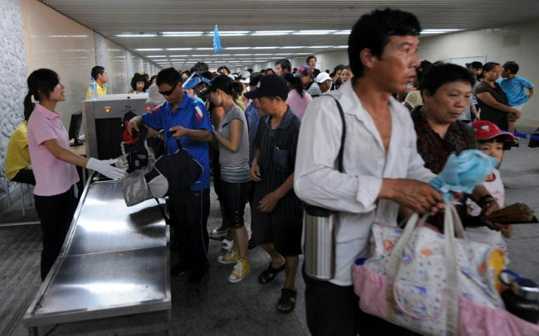 Chinese plainclothes security check bags of tourists as they enter Tiananmen Square in August 2008 ahead of the Olympics when Beijing warned of attacks by the shadowy East Turkestan Islamic Movement, which the United States has concluded does not exist