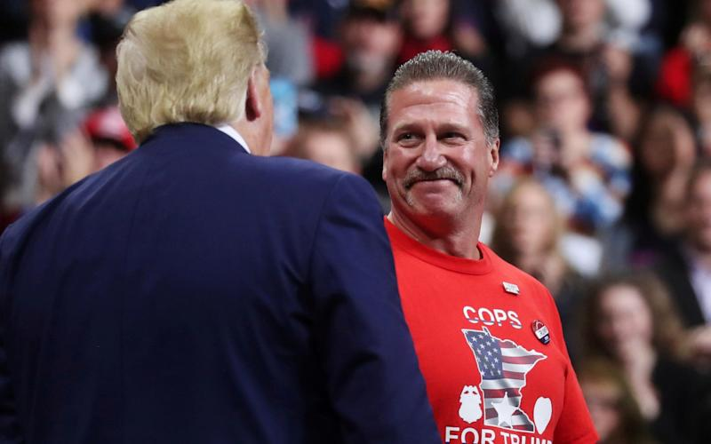 President Donald Trump greets Bob Kroll, president of the Minneapolis police union, during a campaign rally in the city in October 2019 - Leah Mills/Reuters