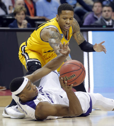 Kansas State's Xavier Sneed, bottom, steals the ball from UMBC's Jairus Lyles, top, defends during the first half of a second-round game in the NCAA men's college basketball tournament in Charlotte, N.C., Sunday, March 18, 2018. (AP Photo/Bob Leverone)