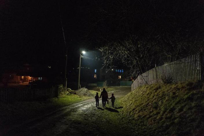 After a long working day Dr. Viktoria Mahnych and her two daughters walk to her parents to celebrate an eve of the Orthodox Christmas in Iltsi village, Ivano-Frankivsk region of Western Ukraine, Wednesday, Jan. 6, 2021. Ukraine is struggling to contain the coronavirus pandemic that has inundated its overburdened medical system, as Dr. Viktoria Mahnych goes door to door providing much needed help to patients.(AP Photo/Evgeniy Maloletka)