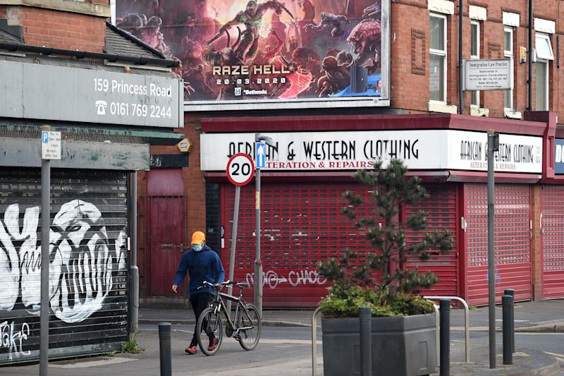 A man wearing a protective face mask wheels his bicycle past shuttered shops in Manchester, north-west England on May 11, 2020, as life in Britain continues during the nationwide lockdown due to the novel coronavirus pandemic. - The British government on Monday published its plan to ease the nationwide coronavirus lockdown in phases in England, with some schools and shops opening from June and recommending people wear face masks in some settings. (Photo by Oli SCARFF / AFP) (Photo by OLI SCARFF/AFP via Getty Images)