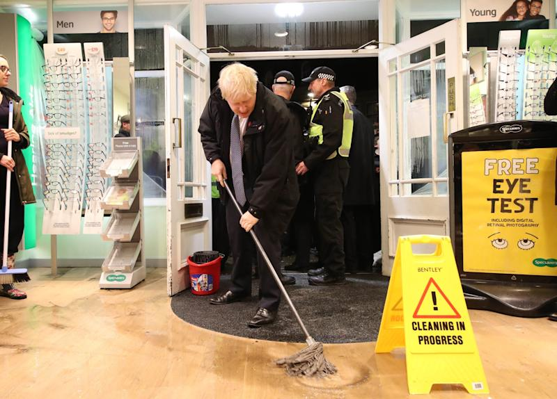 Prime Minister Boris Johnson helps with the clean up at an opticians as he visits Matlock (Getty Images)