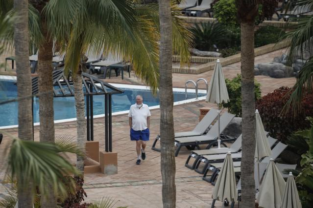 A man walks next the swimming pool of the H10 Costa Adeje Palace hotel in La Caleta, Tenerife (AP)
