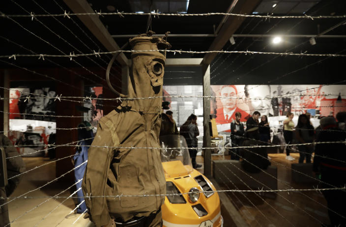 """In this picture taken on Tuesday, Nov. 12, 2019, visitors view the exhibition """"The Technology in Dictatorships,"""" at the National technical Museum in Prague, Czech Republic. The exhibition, the first of that kind here, marks the 30th anniversary of the 1989 anti-communist Velvet Revolution by looking back at the surreal repression of a nation and resistance against it. (AP Photo/Petr David Josek)"""