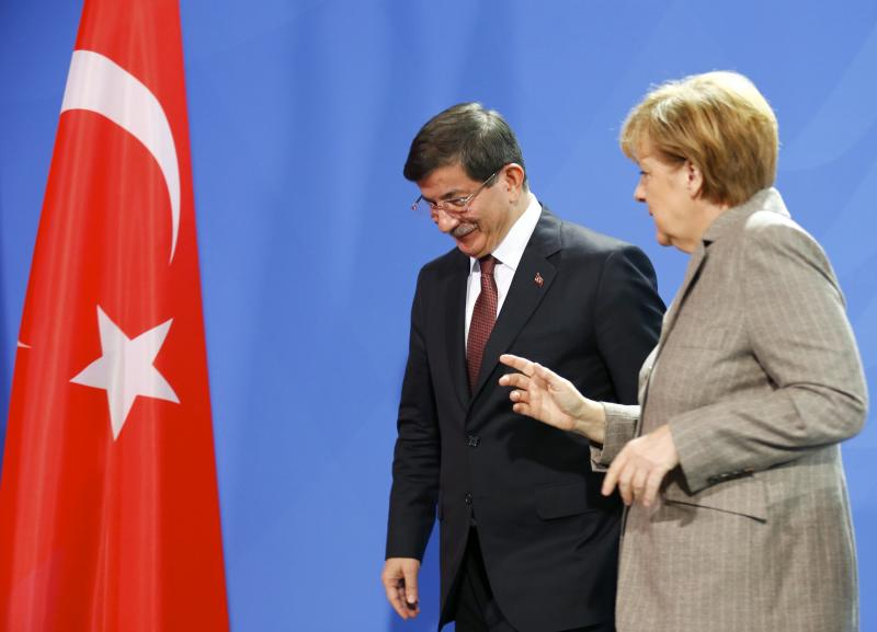 German Chancellor Angela Merkel speaks with Turkish Prime Minister Ahmet Davutoglu after they addressed the media upon their meeting at the Chancellery in Berlin, January 12, 2015.       REUTERS/Hannibal Hanschke (GERMANY  - Tags: POLITICS)