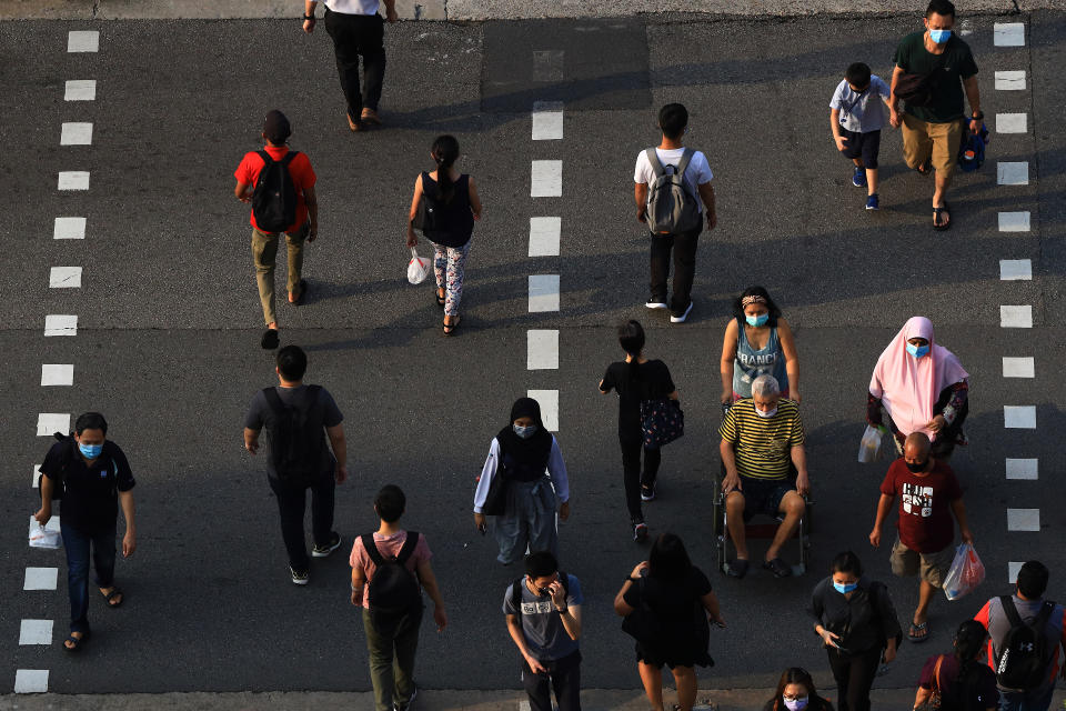 People wearing protective mask cross a street in Singapore.