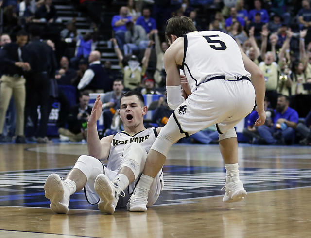 Wofford's Fletcher Magee, left, reacts after drawing a foul on a 3-point shot as Storm Murphy (5) helps him up during the first half against Seton Hall in a first-round game in the NCAA mens college basketball tournament in Jacksonville, Fla., Thursday, March 21, 2019. (AP Photo/Stephen B. Morton)