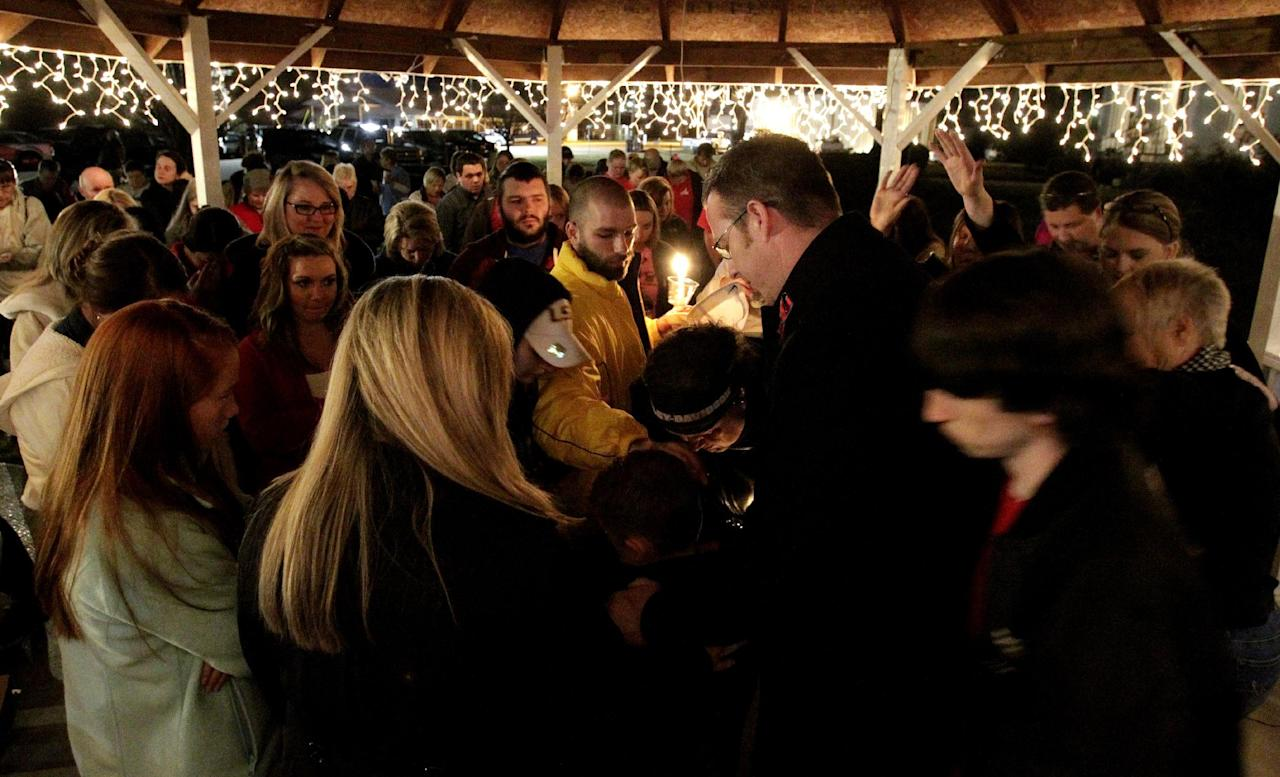 Members of the community gather to pray for a 5-year-old taken hostage, in Midland City, Ala., Sunday, Feb. 3, 2013. Authorities say Jim Lee Dykes, 65 — a decorated Vietnam-era veteran known as Jimmy to neighbors — gunned down a school bus driver and then abducted a 5-year-old boy from the bus, taking him to an underground bunker on his rural property. The driver, 66-year-old Charles Albert Poland Jr., who was shot trying to protect children on his bus, was buried Sunday. (AP Photo/Butch Dill)