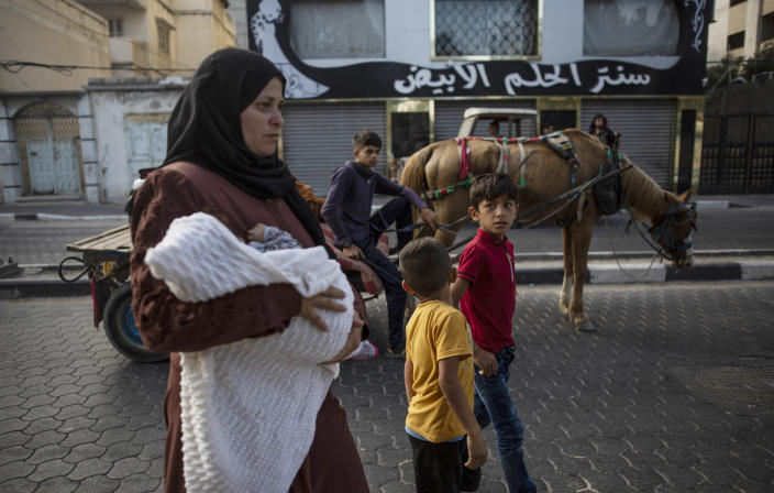 Palestinians flee their homes after overnight Israeli heavy missile strikes on their neighborhoods in the outskirts of Gaza City, Friday, May 14, 2021. (AP Photo/Khalil Hamra)