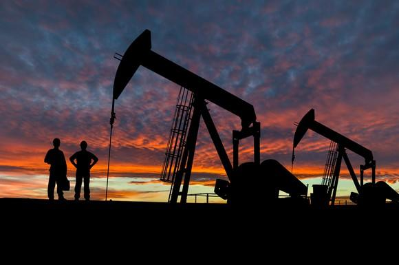Rig workers and oil pumps in silhouette