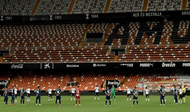 Players observe a minute's silence for coronavirus victims before the derby between Valencia and Levante at Mestalla (AFP Photo/JOSE JORDAN)