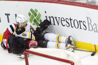 Boston Bruins defenseman Mike Reilly (6) and New Jersey Devils center Jack Hughes (86) collide against the boards behind the Bruins net during the second period of an NHL hockey game, Tuesday, May 4, 2021, in Newark, N.J. Hughes left the game after the collision. (AP Photo/Kathy Willens)