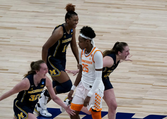 Michigan players celebrate while Tennessee guard Jordan Horston (25) walks off the court after their college basketball game in the second round of the women's NCAA tournament at the Alamodome in San Antonio, Tuesday, March 23, 2021. Michigan won 70-55. (AP Photo/Charlie Riedel)
