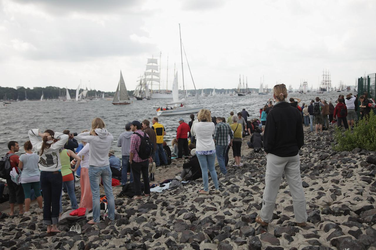 KIEL, GERMANY - JUNE 23:  Visitors watch the Windjammer Parade of tall ships on June 23, 2012 in Kiel, Germany. The parade, which features approximately 100 tall ships and traditional large sailing ships, is the highlight of the Kieler Woche annual sailing festival, which this year is celebrating its 130th anniversary and runs from June 16-24.  (Photo by Sean Gallup/Getty Images)