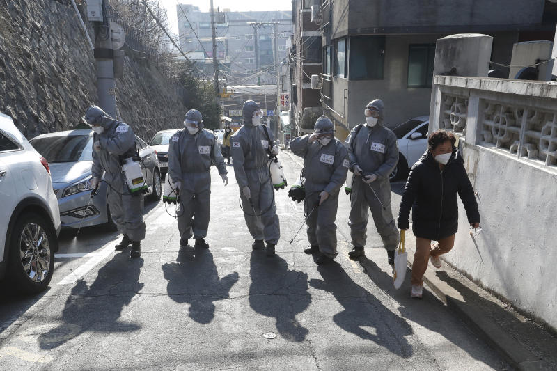 South Korean army soldiers spray disinfectant as a precaution against the coronavirus on a street in Seoul, South Korea, Thursday, March 5, 2020. Italy closed all schools and universities and barred fans from all sporting events for the next few weeks, as governments trying to curb the spread of the coronavirus around the world resorted to increasingly sweeping measures that transformed the way people work, shop, pray and amuse themselves.(AP Photo/Ahn Young-joon)