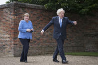 British Prime Minister Boris Johnson shows the way to Chancellor of Germany, Angela Merkel, left, before their bilateral meeting at Chequers, the country house of the Prime Minister of the United Kingdom, in Buckinghamshire, England, Friday July 2, 2021. Johnson is likely to push Angela Merkel to drop her efforts to impose COVID-19 restrictions on British travelers as the German chancellor makes her final visit to Britain before stepping down in the coming months. Johnson will hold talks with Merkel at his country residence on Friday. (Stefan Rousseau/Pool Photo via AP)