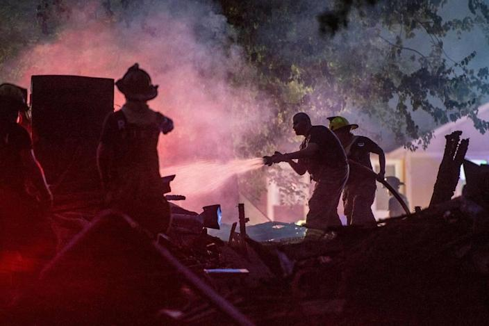 Raytown firefighters spray water on a duplex that exploded in the 7500 block of Englewood Avenue, Monday, June 28, 2021 in Raytown. The cause of the fire is still under investigation.