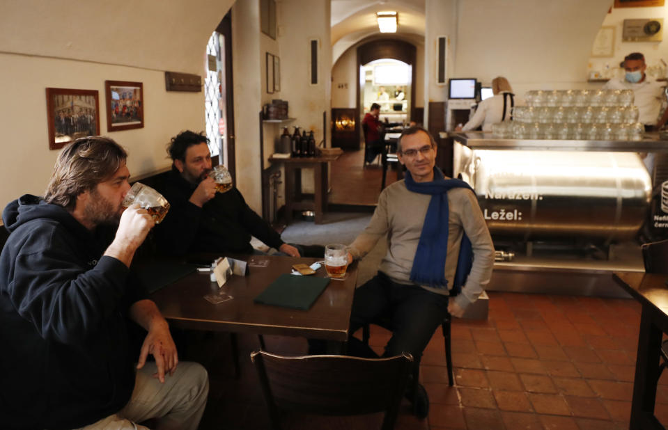 Men enjoy a beer at a pub in Prague, Czech Republic, Thursday, Dec. 3, 2020. A sign of normalcy has returned to the Czech Republic ahead of the Christmas period after the government eased some of its most restrictive measures imposed to contain the recent massive surge of coronavirus infections. On Thursday all stores, shopping malls, restaurants, bars and hotels were allowed to reopen. (AP Photo/Petr David Josek)