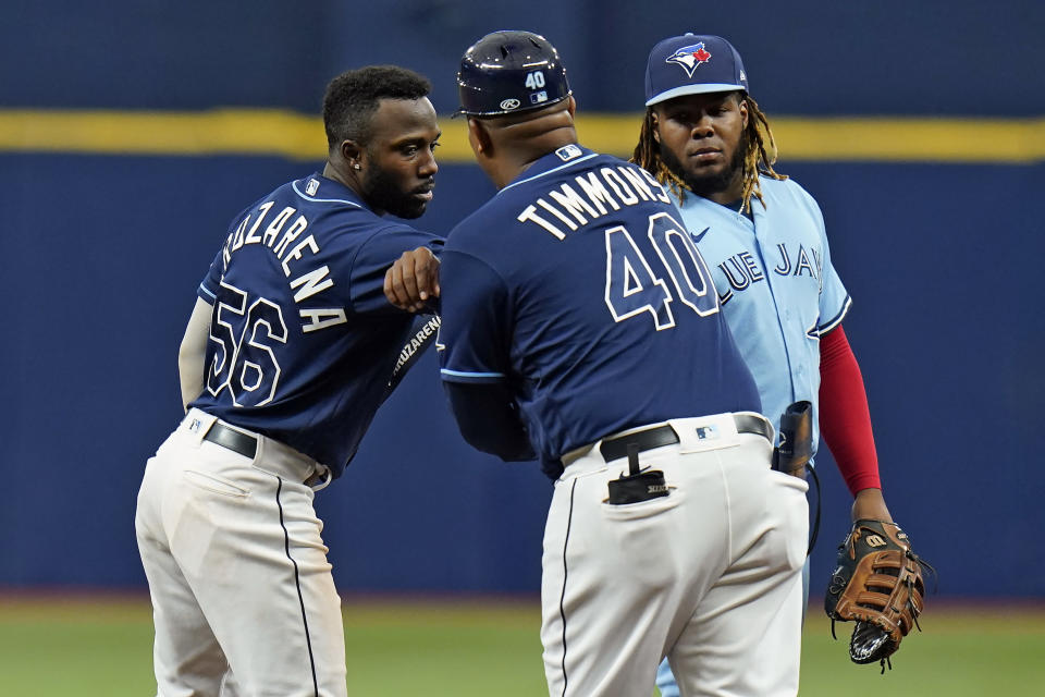 Tampa Bay Rays' Randy Arozarena (56) celebrates with first base coach Ozzie Timmons (40) after his double off Toronto Blue Jays pitcher Ross Stripling during the third inning of a baseball game Wednesday, Sept. 22, 2021, in St. Petersburg, Fla. Looking on is Blue Jays' Vladimir Guerrero Jr.(AP Photo/Chris O'Meara)