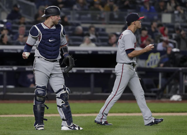 Minnesota Twins catcher Mitch Garver, left, and pitcher Jose Berrios react after Garver misplayed a ball hit by New York Yankees' Miguel Andujar during the fourth inning of a baseball game Tuesday, April 24, 2018, in New York. (AP Photo/Julie Jacobson)
