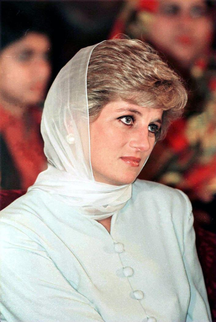 Princess Diana looks to the right wearing a green blouse and matching scarf.