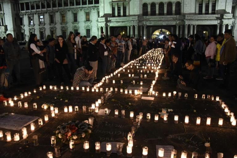 People take part in a protest at the Square of the Constitution in Guatemala City on March 9, 2017, following the death of 40 girls in a recent fire at a government-run children's shelter in San Jose Pinula, east of the capital