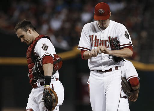 Arizona Diamondbacks' Patrick Corbin, right, rubs up a new ball after getting a visit from catcher Miguel Montero, after Corbin gives up a run to the San Francisco Giants during the seventh inning in a baseball game Friday, June 7, 2013, in Phoenix. (AP Photo/Ross D. Franklin)