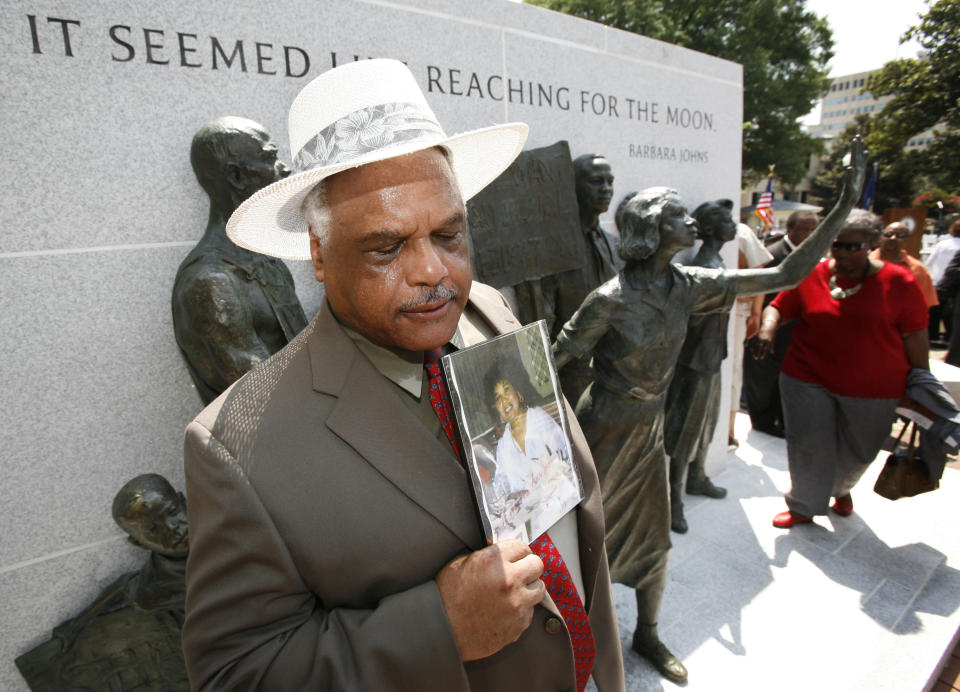 FILE - In this July 21, 2008, file photo, Roderick Johns, brother of Civil Rights activist Barbara Johns, takes a moment as he holds a photo of his sister at the newly dedicated Virginia Civil Rights Memorial on the grounds of the State Capitol in Richmond, Va. There will soon be a statue saluting Virginia's Barbara Johns, a 16-year-old Black girl who staged a strike in 1951 over unequal conditions at her segregated high school in Farmville. Her actions led to court-ordered integration of public schools across the U.S, via the landmark Supreme Court decision, Brown v. Board of Education. (AP Photo/Steve Helber, File)